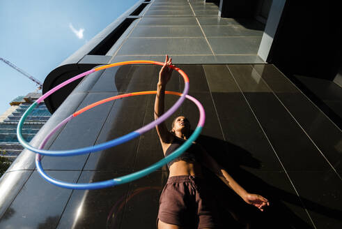 Sporty woman exercising with plastic hoops outside modern building - JMPF00100