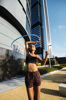 Sporty woman exercising with plastic hoops on sidewalk outside office buildings - JMPF00103