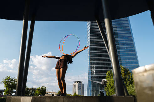 Sporty woman balancing plastic hoops on chest in modern city - JMPF00112
