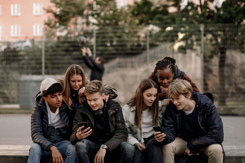 Multi-ethnic teenage friends using smart phones while sitting at park in city - MASF18501