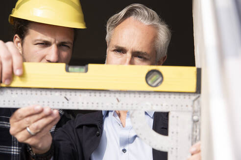 Close-up of architect and construction worker measuring window frame seen through outdoors - MJFKF00431