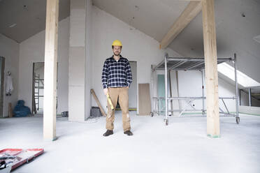 Confident construction worker standing at renovating home - MJFKF00437