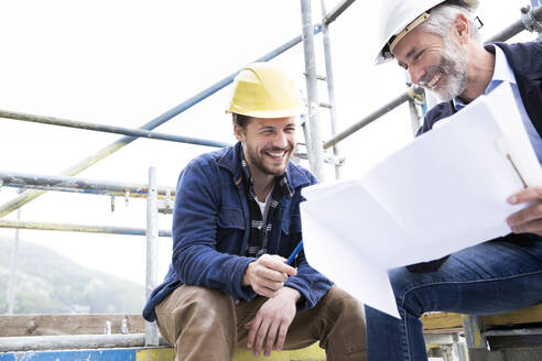 Smiling architect and construction worker discussing blueprint while sitting against clear sky at construction site - MJFKF00443