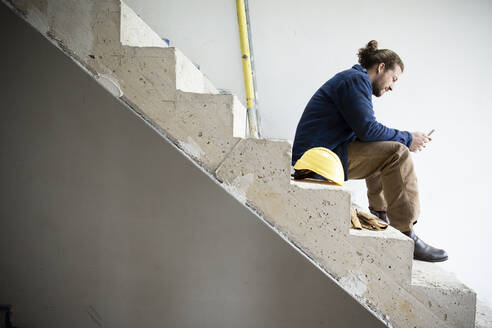 Construction worker using smart phone while sitting on steps in house at site - MJFKF00461