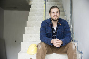 Thoughtful construction worker sitting on steps in house under construction - MJFKF00464