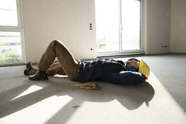 Construction worker with hands behind head sleeping on floor in house under construction - MJFKF00470