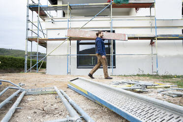 Construction worker carrying plank at construction site - MJFKF00479