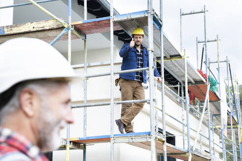 Construction worker showing thumbs up to coworker while sitting on scaffold at site - MJFKF00485