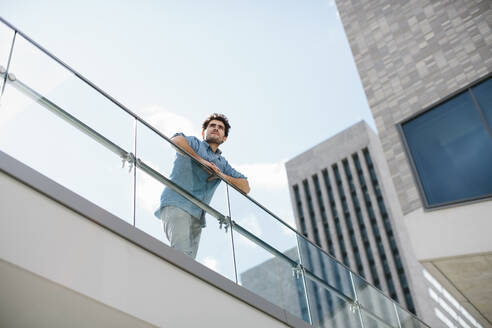 Thoughtful businessman looking away while standing by railing against sky - SODF00821