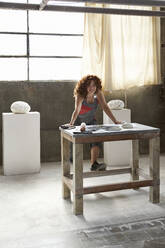 Mid adult woman posing while standing by workbench in workshop - VEGF02448