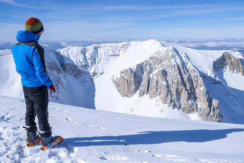 Young man looking at view while standing on snowcapped mountain, Umbrian, Italy - LOMF01184