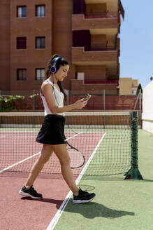 Valencia, Spain. A sporty woman on a tennis court, with the smartphone in her hand and headphones, on a sunny day. - EGAF00425