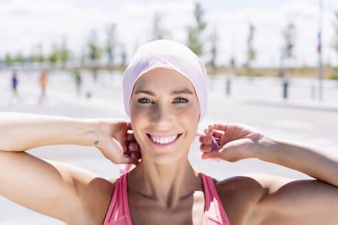 Happy sporty woman tying headscarf on street - JCMF00946