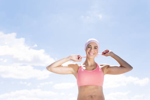 Happy sporty woman wearing headscarf while standing against blue sky - JCMF00949