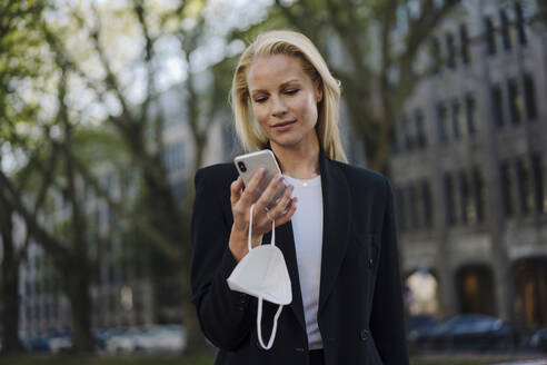 Beautiful businesswoman using mobile phone while standing in city - JOSEF00967
