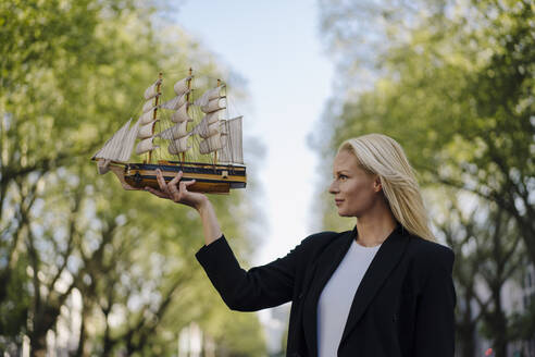 Confident blond mid adult businesswoman looking at model sailboat in city - JOSEF00976