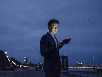 Mature businessman using tablet at the riverbank at dusk - JOSEF01227