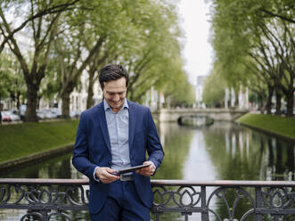 Mature businessman standing on a bridge using tablet - JOSEF01230