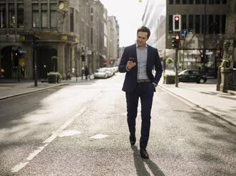 Mature businessman walking on a city street using smartphone - JOSEF01236
