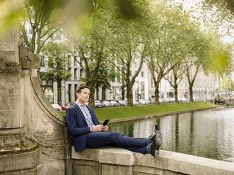 Mature businessman with smartphone sitting on a bridge balustrade - JOSEF01242