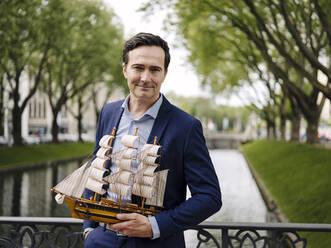 Portrait of a confident mature businessman holding model sailing ship on a bridge - JOSEF01248