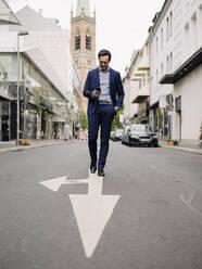 Mature businessman walking on a city street using smartphone - JOSEF01254