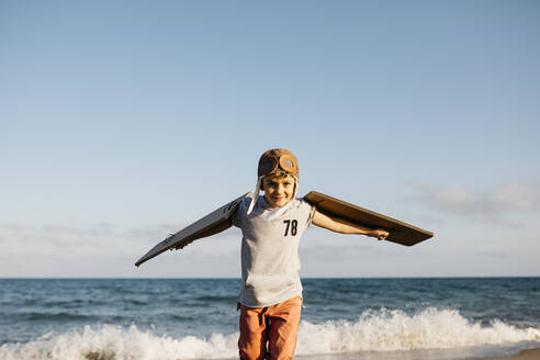 Boy wearing aviator's cap and cardboard wings at beach - JRFF04561