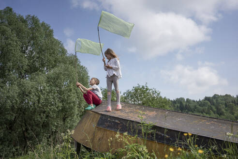 Friends catching butterflies with nets on abandoned boat against sky - VPIF02541