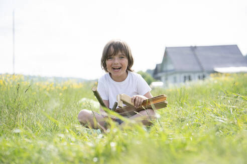 Cheerful cute boy holding model airplane while sitting on grassy land against clear sky - VPIF02550