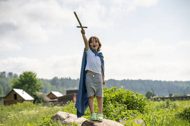 Playful boy wearing cape holding toy sword while standing on rock against sky - VPIF02553