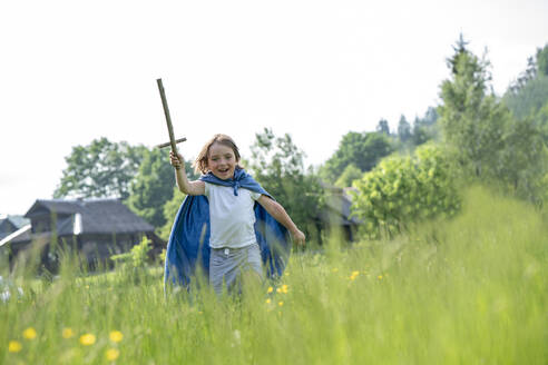 Playful boy wearing cape holding toy sword while running on grassy land against clear sky - VPIF02556