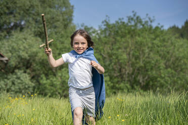 Playful boy wearing cape holding toy sword while running on grassy land - VPIF02559