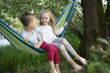 Girl talking with boy while sitting on hammock in forest - VPIF02565