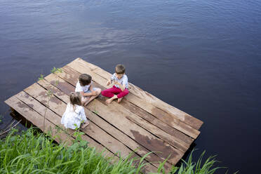 Children playing on pier over lake in forest - VPIF02568