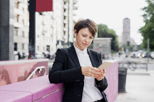 Confident businesswoman using smart phone while standing by retaining wall in city - MEUF01214