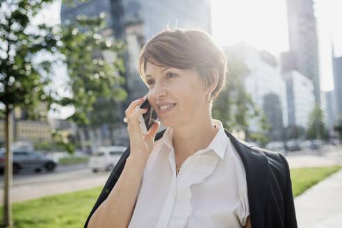 Close-up of businesswoman with short hair talking over smart phone in city - MEUF01232