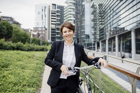 Smiling female professional with bicycle standing on footpath in city - MEUF01262