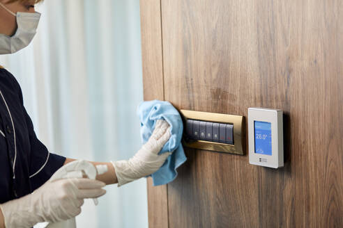 Chambermaid wearing mask wiping push buttons on wall in hotel - ZEDF03500