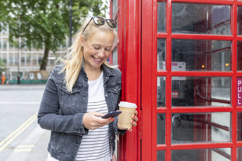 Smiling woman holding coffee cup using smart phone while standing by telephone booth - WPEF03166