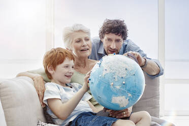 Grandmother, father and grandson sitting on couch in a villa looking at globe - RORF02251