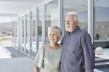 Happy senior couple standing at luxury beach house - RORF02266