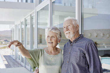 Portrait of senior couple at luxury beach house looking at view - RORF02269