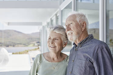 Portrait of smiling senior couple at luxury beach house - RORF02272