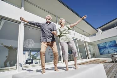 Carefree senior couple having fun at luxury beach house - RORF02275
