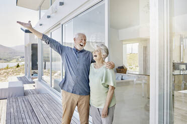 Carefree senior couple standing at luxury beach house - RORF02299