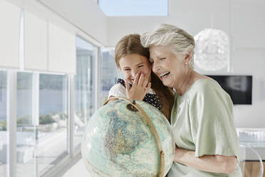 Laughing grandmother and granddaughter with globe in a villa - RORF02305