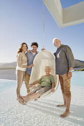 Portrait of happy senior couple with adult children at hanging chair above swimming pool - RORF02320