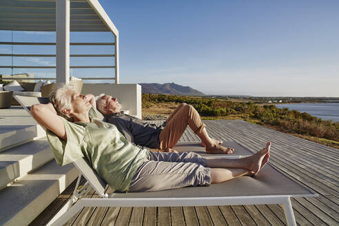 Senior couple lying on deck chairs at luxury beach house - RORF02329