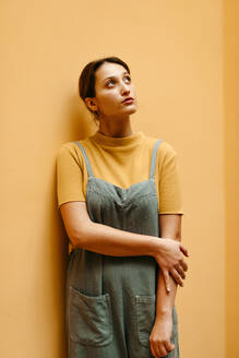Young woman wearing jumpsuit leaning on orange wall and looking up - TCEF00899