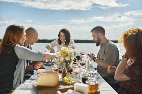 Friends having dinner at a lake - ZEDF03530